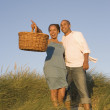 Couple with picnic basket at beach - Stock Photo