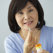 Senior Asian woman taking medication — Stock Photo