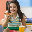 Four girls eating pizza in cafeteria — Stock Photo #13235491