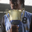 Royalty-Free Stock Photo: Male soccer player proudly holding trophy