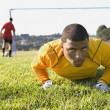 African male soccer player in grass - Stock Photo