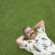 Mature man relaxing on green lawn — Stock Photo