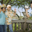 Young man using video camera to film senior couple waving — Stock Photo