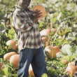 African boy holding pumpkin in pumpkin patch — Stock Photo