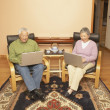 Senior Asian couple having tea while using laptops — Stock Photo