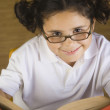 Hispanic girl wearing eye glasses and reading book — Stock Photo #13235562