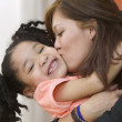 Portrait of mother hugging and kissing young daughter — Stock Photo
