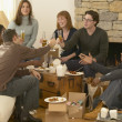 Group of friends toasting over take out food — Stock fotografie
