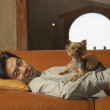 Portrait of man laying on couch with dog — Stok fotoğraf