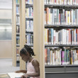 Stock Photo: Girl reading book in library