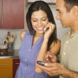 Hispanic couple using cell phone and electronic organizer — Stock Photo