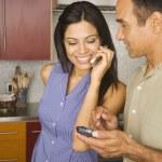 Hispanic couple using cell phone and electronic organizer — Stock Photo #13235628