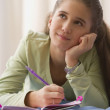 Stock Photo: Hispanic girl writing in diary on bed