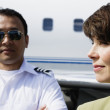 Businesswoman and male pilot standing in front of private airplane - Stock Photo