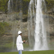 Man with hard hat and clipboard looking at waterfall — Stock Photo #13235652