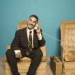 Portrait of businessman in chair talking on phone - Stock Photo