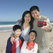 Family taking a self-portrait on the beach — Stock Photo