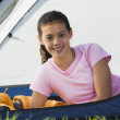 Teenage girl smiling for the camera in a tent - Stock Photo