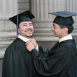 Graduate tying colleague's collar - Stock Photo