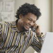 Royalty-Free Stock Photo: African man using telephone and laptop