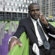 Businessman sitting on bench talking on cell phone — Stock Photo