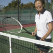 Senior Asian woman laughing on tennis court — Stock Photo
