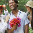 Man holding flowers between two women — Stock Photo