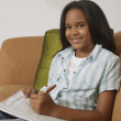 African girl writing in notebook on sofa — Stock Photo