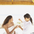 Spa employee pouring a glass of water for woman sitting on massage table — Stock Photo #13235796