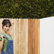 Hispanic woman painting fence — Foto de Stock