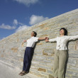 Asian couple leaning on a wall outdoors — Stock Photo