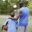 Stock Photo: Father and son looking at basketball court