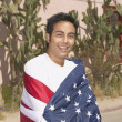 Young man draped in an American flag — Stock Photo
