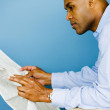 African man reading newspaper — Stock Photo
