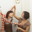 Stock Photo: Young woman trying on a sweater in fitting rooms