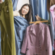 Woman covered with curtain from dressing room looking at clothes - Stock fotografie