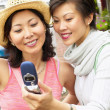 Two women taking picture with cell phone — Stock Photo #13235955