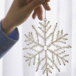 Woman holding a snowflake decoration — Stock Photo