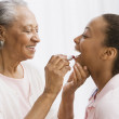 Stock Photo: Africgrandmother helping granddaughter apply lipstick
