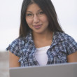 Asian woman smiling with laptop at beach — Stock Photo