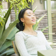 Woman sitting with eyes closed outdoors — Stock Photo