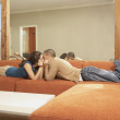 Young Hispanic couple lying on the sofa kissing  — Stock Photo