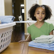 African girl with folded laundry — Stock Photo