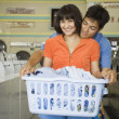 Couple with laundry hugging at laundromat - Stockfoto