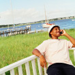 Young man using cell phone at waterfront — Stock Photo