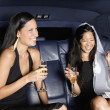 Two women drinking champagne in backseat of car — Stock Photo