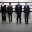 Multi-ethnic businessmen jumping in police line up — Stock Photo #13236115