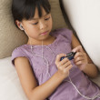 Young Asian girl listening to mp3 player on sofa — Stock Photo