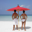 Couple standing under an umbrella on the beach — Stock Photo #13236145