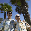 Father and adult son wearing sunglasses and Hawaiian shirts — Stock Photo
